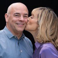 Portrait of woman kissing man's cheek