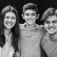 Black and white natural light portrait of three siblings on black background
