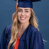 Natural light portrait of a young woman in graduation cap and gown on a blue background