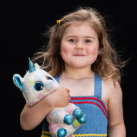 Natural light portrait of a little girl with a stuffed unicorn on black background